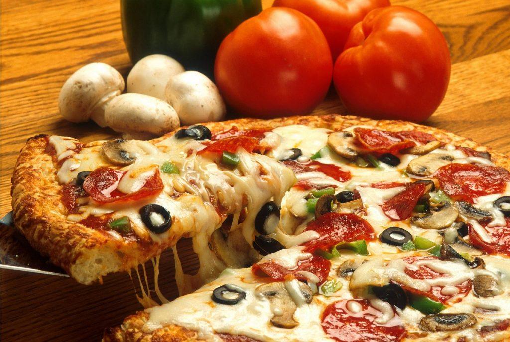 Vemos, em foco, uma pizza com salaminho, azeitonas pretas, pedaços de pimentão e muito queijo enquanto, é possível imaginar, vemos alguém retirando uma fatia com ma espátula. Ao fundo temos alguns tomates e cogumelos.