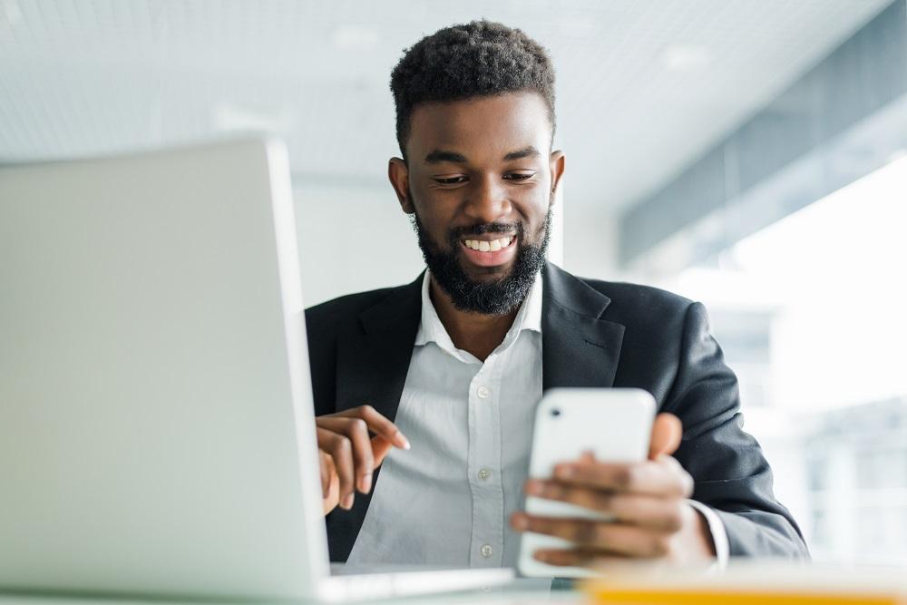 Homem de roupa social, segurando um celular com um computador do lado. Ao fundo vemos uma janela ampla e clara. Ilustração do texto franquias para investir em 2021.