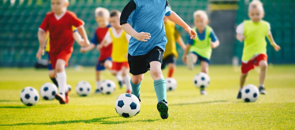 Vemos várias crianças correndo em um campo de futebol (imagem ilustrativa).