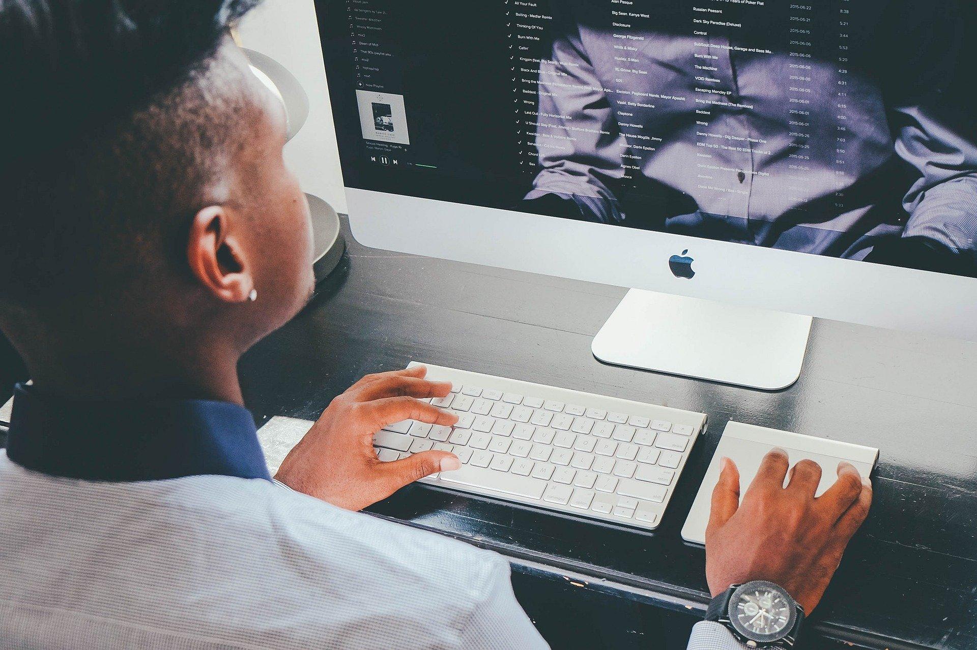 Vemos um homem na frente de um computador enquanto trabalha (imagem ilustrativa). Texto: franquias baratas.