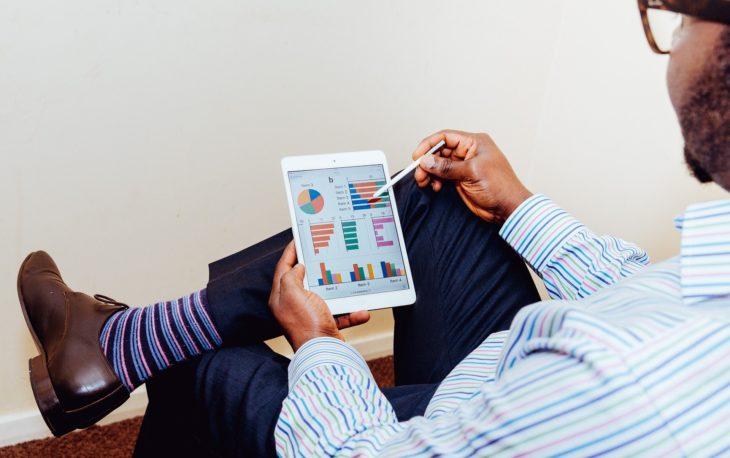 homem analisando tela de tablet franquias investir 2020