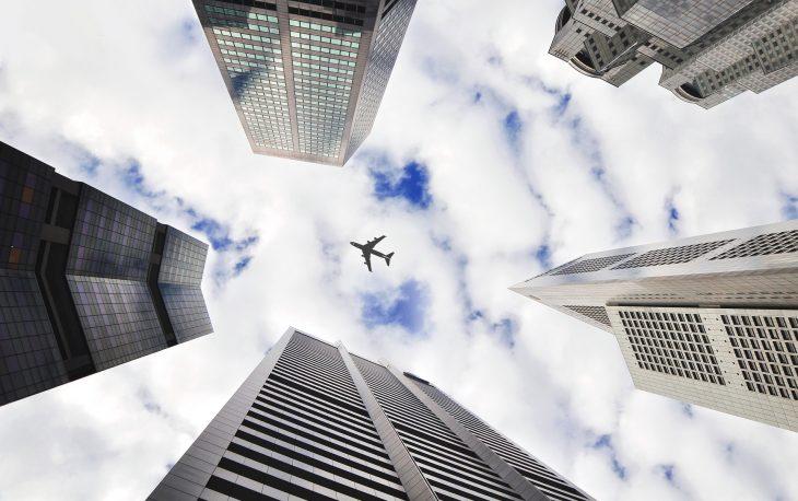 Imagem de uma foto do céu com um avião passando por sobre prédios. Imagem ilustrativa texto franquias com menos de 50 mil.