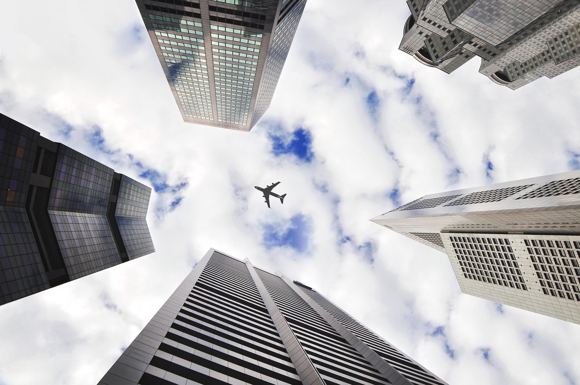 Vemos, de baixo para cima, o céu com um avião passando por sobre alguns prédios gigantescos (imagem ilustrativa). Texto: franquias com menos de 50 mil.