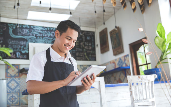 homem feliz dentro da sua loja ilustrativo texto como abrir uma franquia