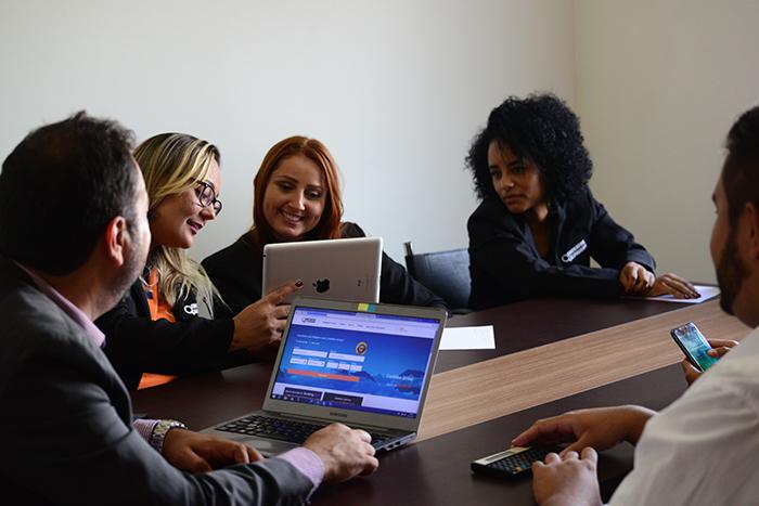 Imagem de mulheres em uma mesa de trabalho olhando para um computador. Imagem ilustrativa texto tendências de franquias 2022.