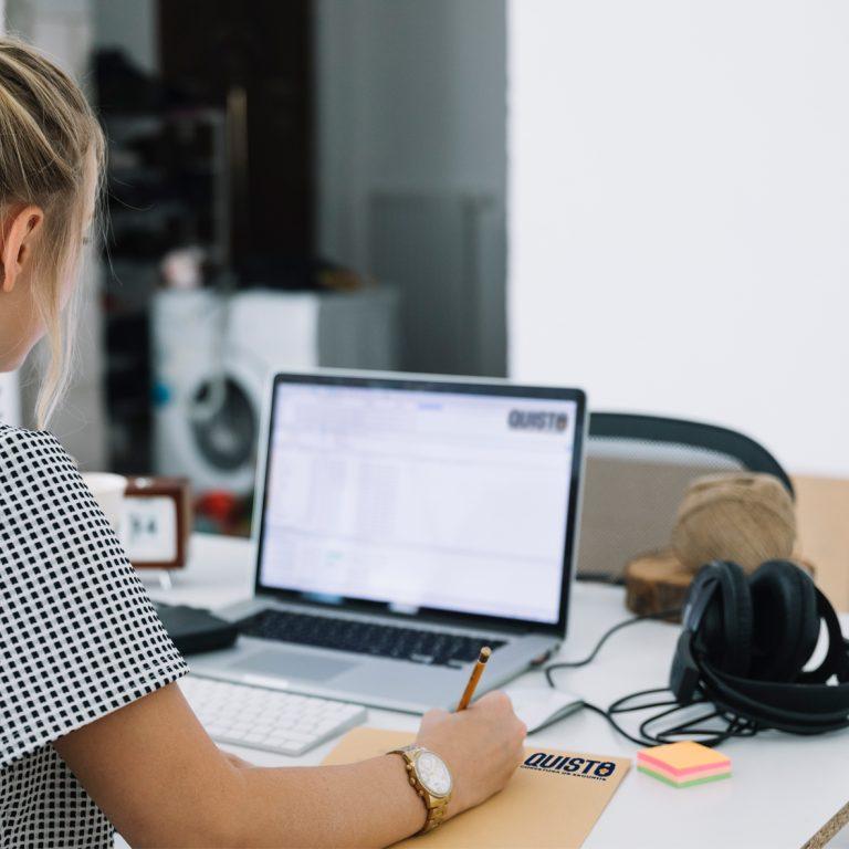 moça trabalhando sentada à uma mesa com um notebook à sua frente na franquia quisto corretora de seguros
