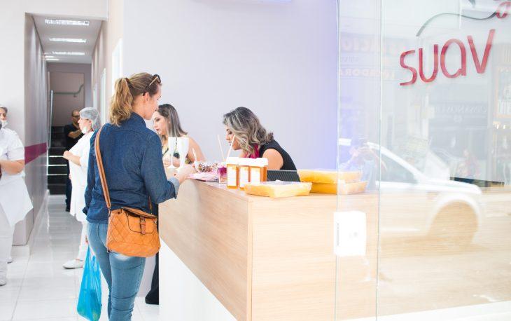 Vemos uma loja da Suav, com uma atendente e uma cliente no balcão da recepção (imagem ilustrativa). Texto: qual melhor tipo de negócio para abrir.