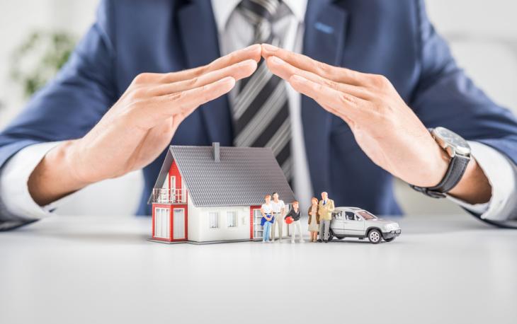 Imagem de uma pessoa com a mãos em cima de miniaturas de casa e carro. Imagem ilustrativa texto franquia touareg seguros.