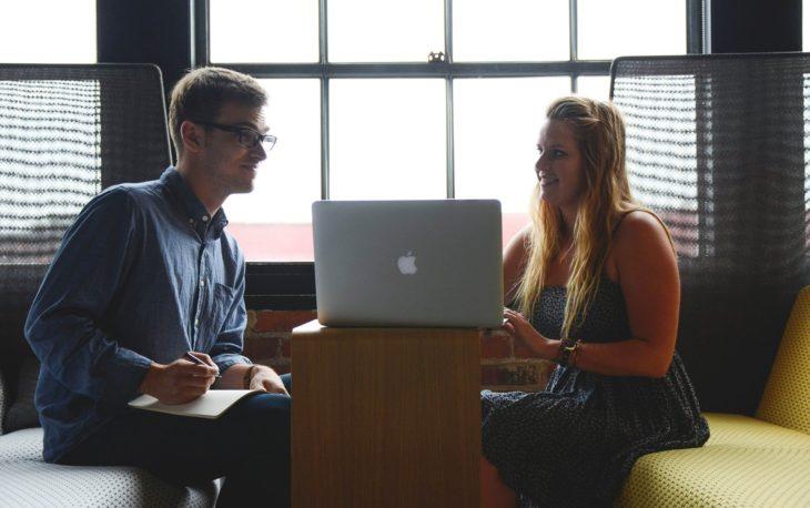 jovens empreendedores sentados em frente ao notebook conversando