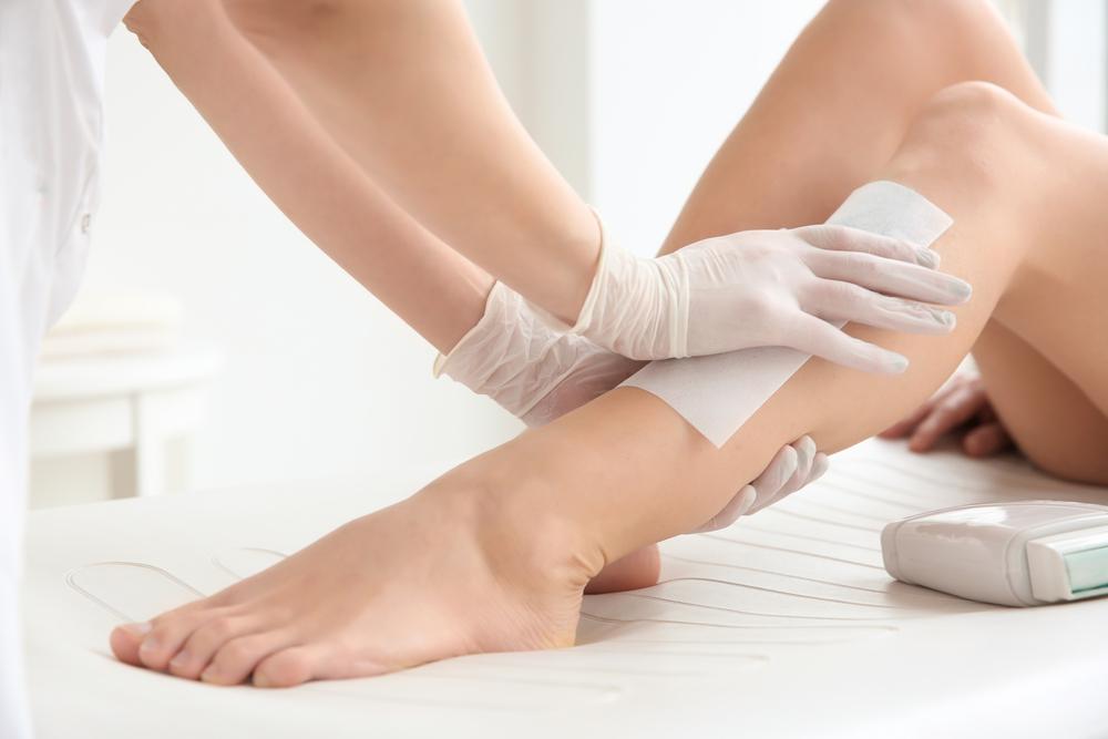 Vemos uma mulher realizar o processo de depilação em uma das pernas (imagem ilustrativa). Texto: modelos de franquias de beleza.