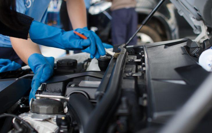 Vemos uma pessoa fazendo a limpeza de um motor (imagem ilustrativa). Texto: empreendedorismo feminino.