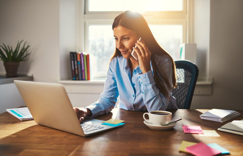 Vemos uma mulher em seu escritório, em casa, realizando uma chama ao celular enquanto consulta algo em seu notebook. Ao lado vemos algumas folhas para anotação e uma xícara de café (imagem ilustrativa).