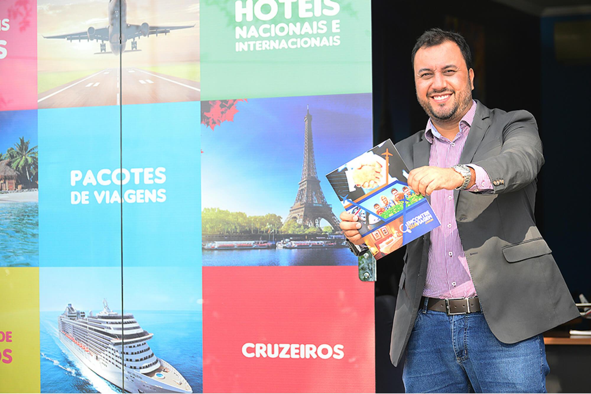 Vemos Henrique Mol, presidente do grupo Encontre Sua Franquia, segurando um guia de viagens da Encontre Sua Viagem (imagem ilustrativa). Texto: franquia de agência on-line de turismo.
