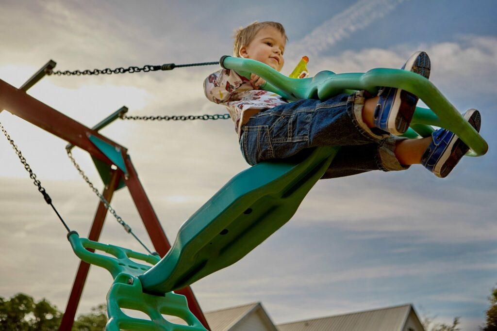 Criança em um balanço verde, vemos parte do céu e do brinquedo. Imagem ilustrativa para texto franquias para o público infantil.