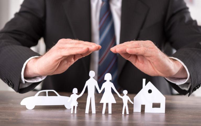 Imagem de uma pessoa com a mãos sobre bonecos simbolizando ma família, carro e casa. Imagem ilustrativa texto franquia San martin.