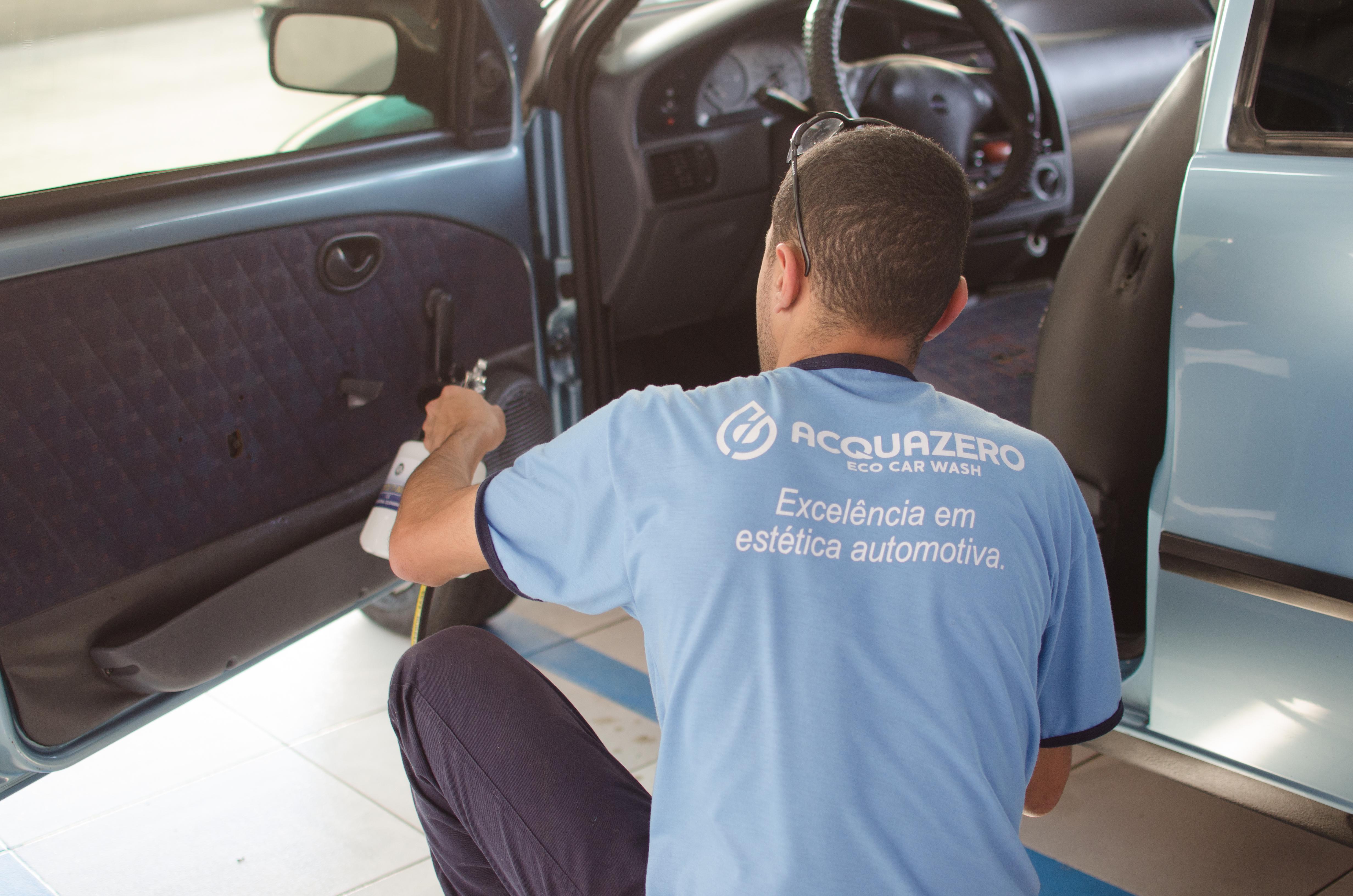 Vemos um técnico da Acquazero limpando porta carro (imagem ilustrativa).