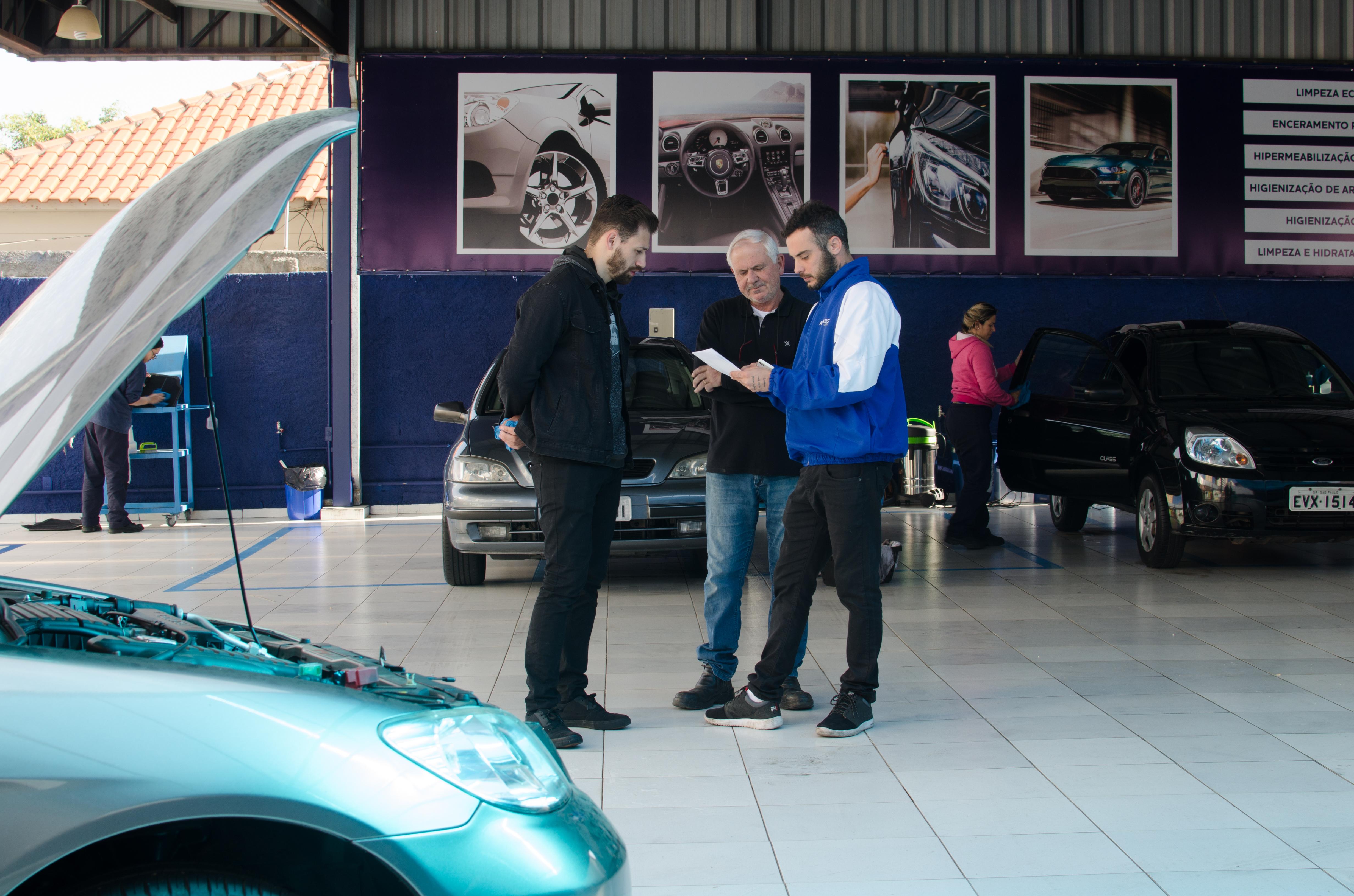 Vemos que um vendedor conversa co dois clientes em uma franquia de serviços automotivos (imagem ilustrativa). Texto: franquia automotiva.