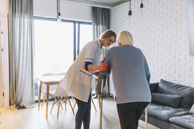 Vemos uma fisioterapeuta realizar o atendimento a uma idosa em casa (imagem ilustrativa). Texto: franquias para idosos.