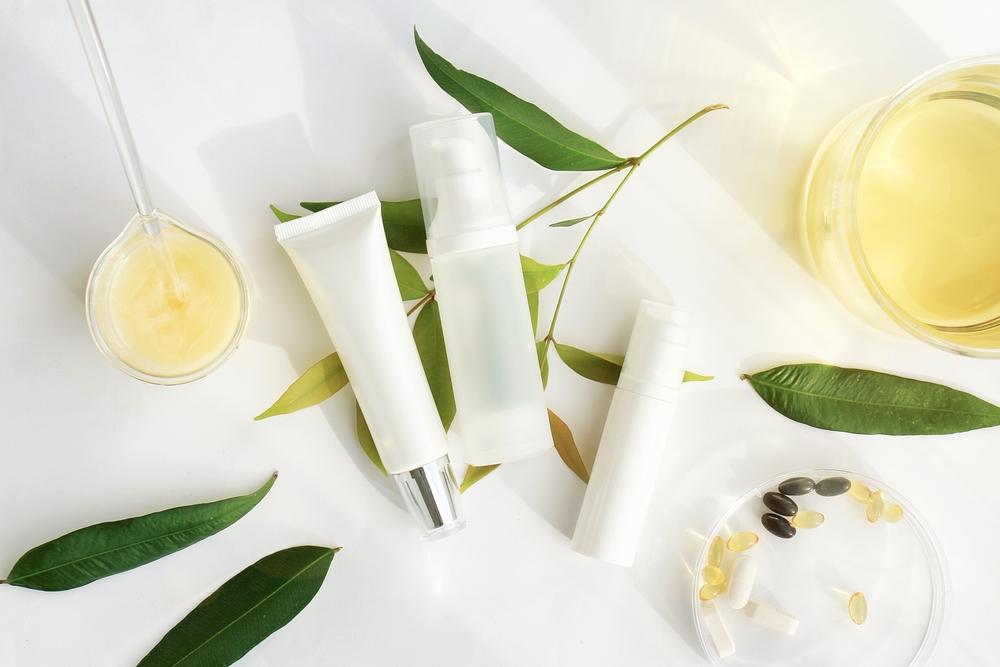 Vemos sobre uma superfície branca alguns potes e frascos de produtos como hidratante corporal, labial e uma de base facial. Ao redor, algumas folhas verdes, pílulas de mineiras e dois béquers (imagem ilustrativa).
