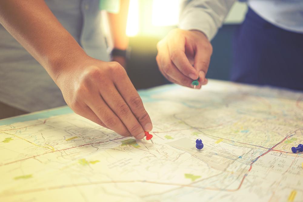 Vemos duas pessoas fixando pins em um mapa-múndi (imagem ilustrativa). Texto: melhores microfranquias 2021.