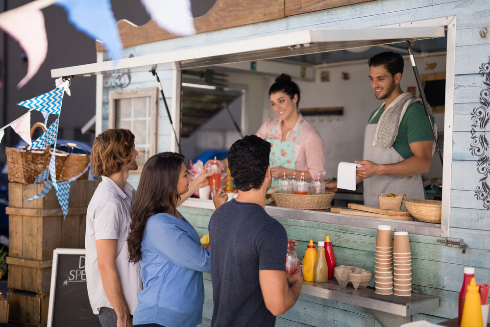 Vemos algumas pessoas sendo atendidas em um food truck (imagem ilustrativa). Texto: mercado de food service.