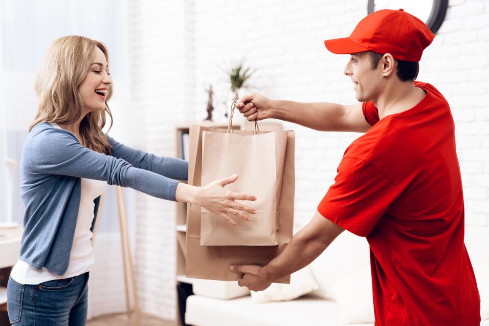 Vemos que um homem de vermelho está realizando a entrega de dois pacotes para uma cliente (imagem ilustrativa).