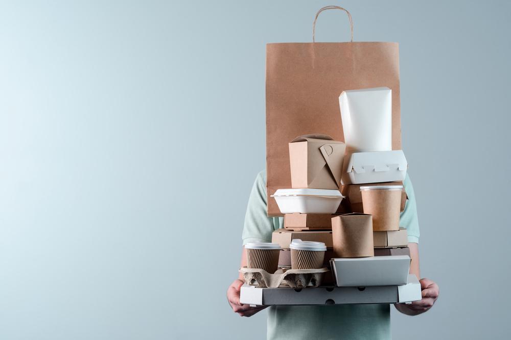 Vemos uma pessoa segurando diversas embalagens de produtos alimentícios, como café, caixa de comida chinesa, de hambúrguer,  rosquinhas, pizza etc (imagem ilustrativa).