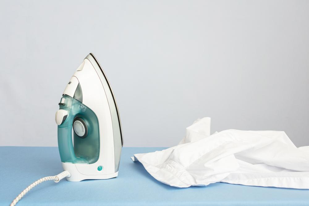 Vemos um ferro de passar e uma camisa branca sobre uma tábua azul (imagem ilustrativa).