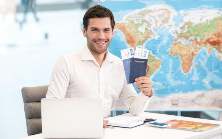 Imagem de um homem segurando dois passaportes. Imagem ilustrativa texto franquia CI Intercâmbio.