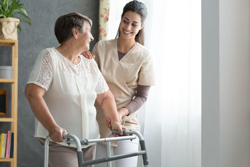 Vemos uma mulher e uma idosa. Sorrindo uma para a outra, a profissional está ajudando a senhora a caminhar (imagem ilustrativa).