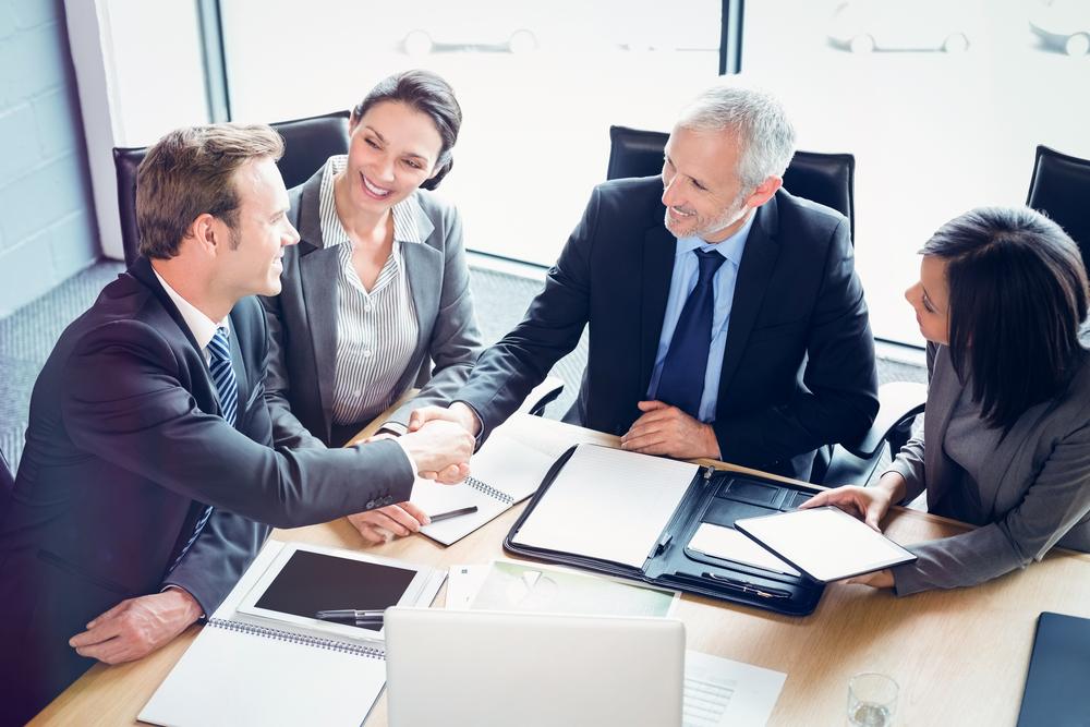 Vemos que alguns empresários, entre homens mulheres, parecem fechar um negócio em uma sala de reuniões (imagem ilustrativa). Texto:
