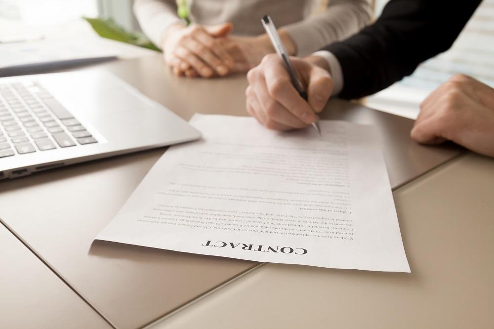 Foto de um homem de roupa preta, assinando um contrato em uma mesa bege. Ao lado vemos um computador e uma mulher de roupa clara. Ao fundo temos uma janela.