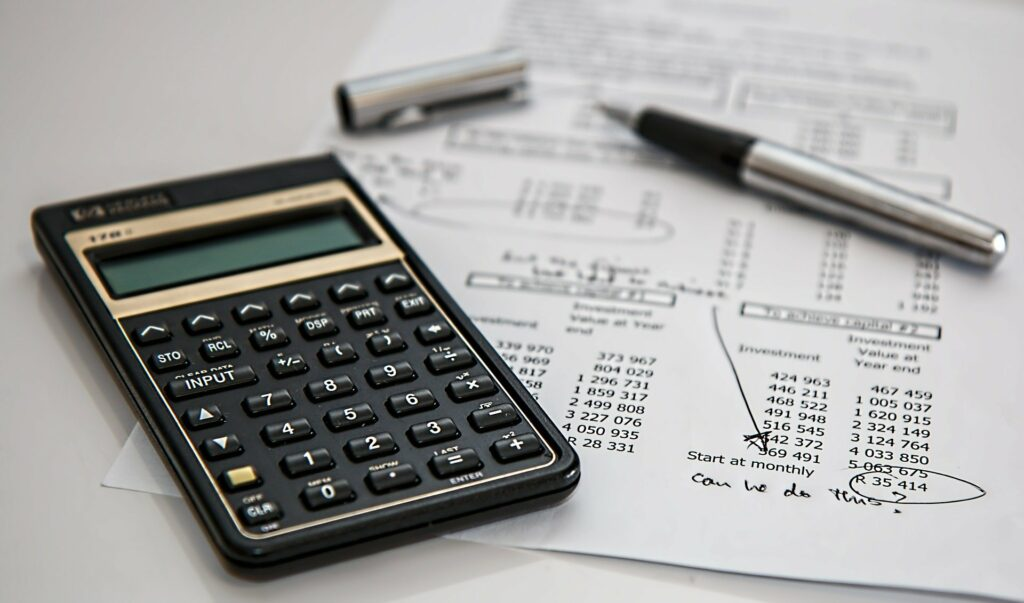 Foto de uma calculadora preta ao lado de um papel branco com números e contas. Ao lado vemos uma caneta prata em um fundo branco.