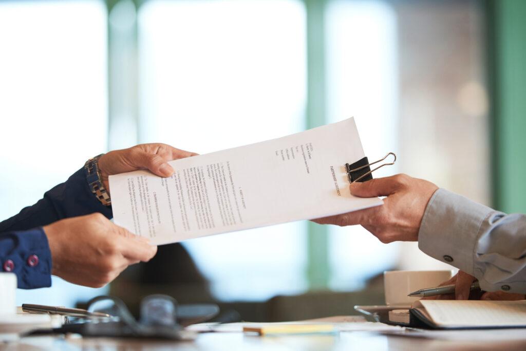 Vemos a mão uma pessoa entregando um contrato nas mãos de outra outra (imagem ilustrativa). Texto: franquias boas e baratas 2021.