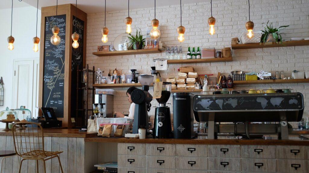 Foto de uma cafeteria, com parede de tijolos branca, balcão marrom e equipamentos de café pretos. Ao fundo vemos prateleiras de madeira com produtos. Temos também uma parede com quadro de escrever, e várias luminárias enquanto um atendente está trabalhando.