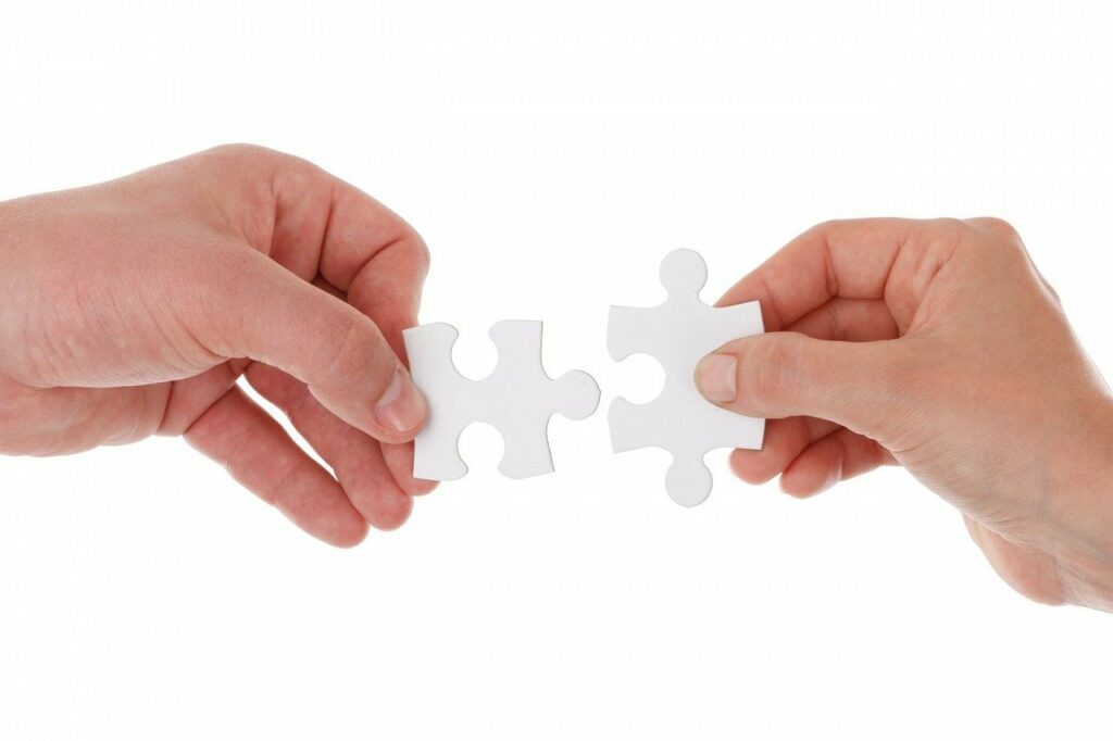 Duas mãos, cada uma segurando uma peça de quebra cabeça que se encaixam. Imagem ilustrativa para texto o que é franquia.