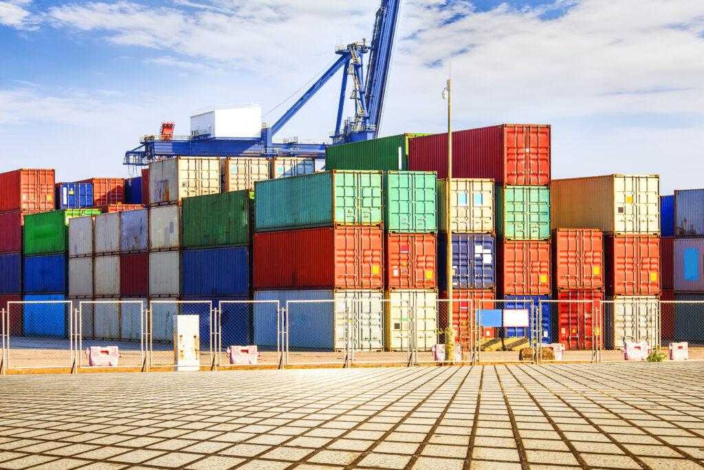 Vemos vários containers empilhados em um porto.