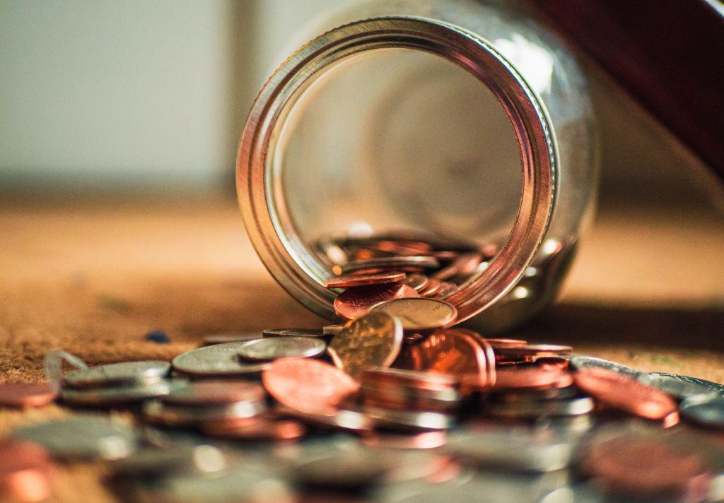Vemos algumas moedas de um pote espalhadas sobre uma mesa (imagem ilustrativa). Texto: pegar empréstimo para abrir uma franquia.