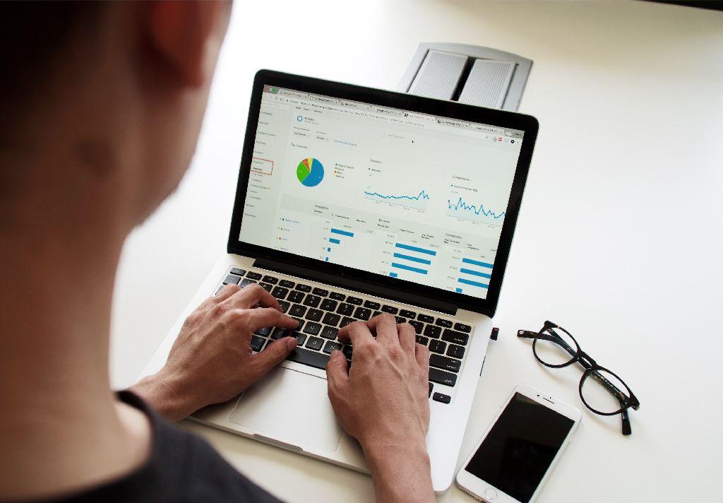 Vemos uma pessoa em seu computador enquanto analisa alguns gráficos em tela (imagem ilustrativa).