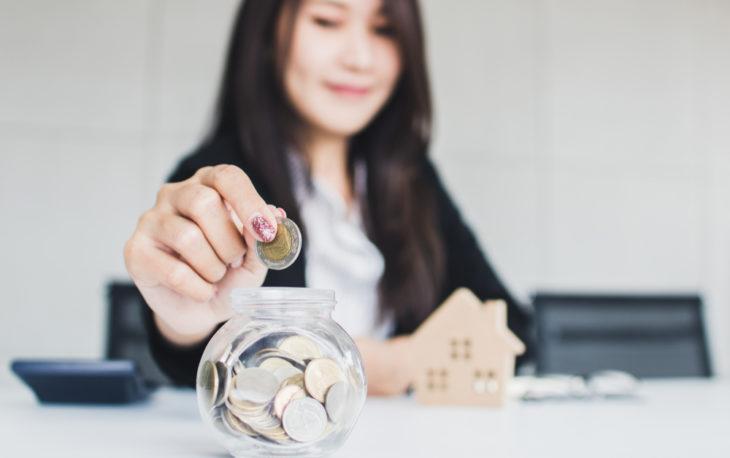 Franquias de até R$ 5 mil: mulher colocando dinheiro em um cofre