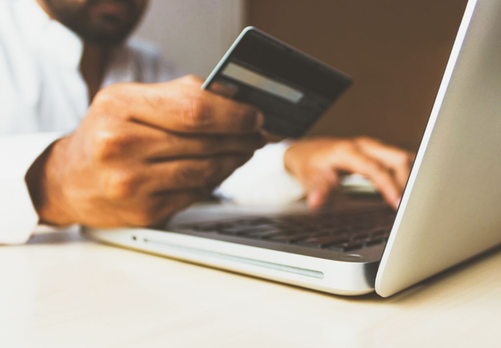 Vemos alguém segurar um cartão de crédito nas mão enquanto realiza uma algum tipo de pesquisa em um notebook (imagem ilustrativa). Texto: franquias baratas home office.