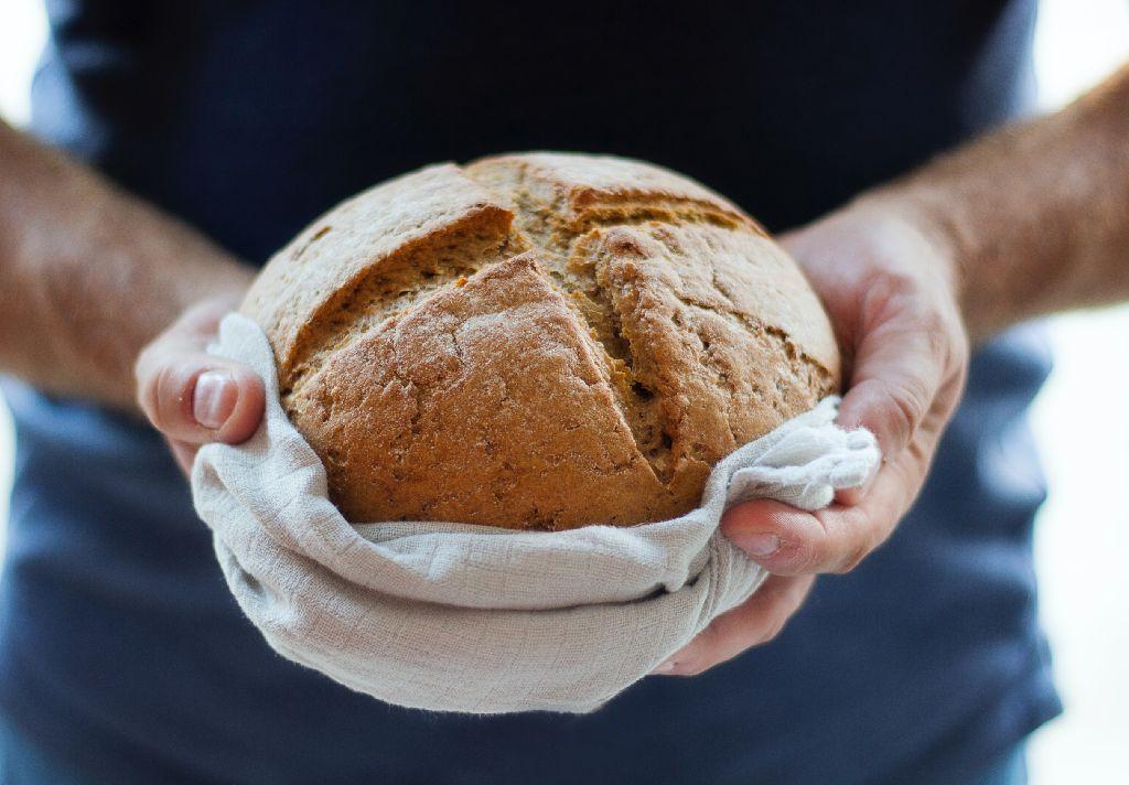 Vemos alguém segurar um pão de fermentação natural (imagem ilustrativa). Texto: franquias baratas home office.