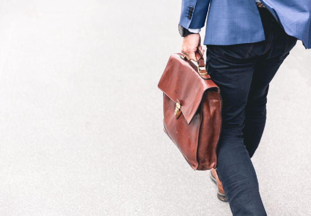 Vemos um homem caminhar com sua maleta de couro (imagem ilustrativa).