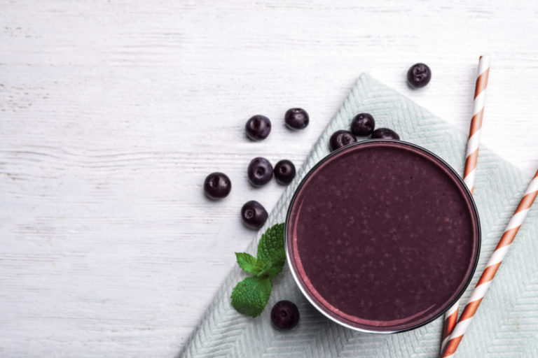 Franquias de açaí: Copo com uma vitamina de açaí e alguns frutos ao lado