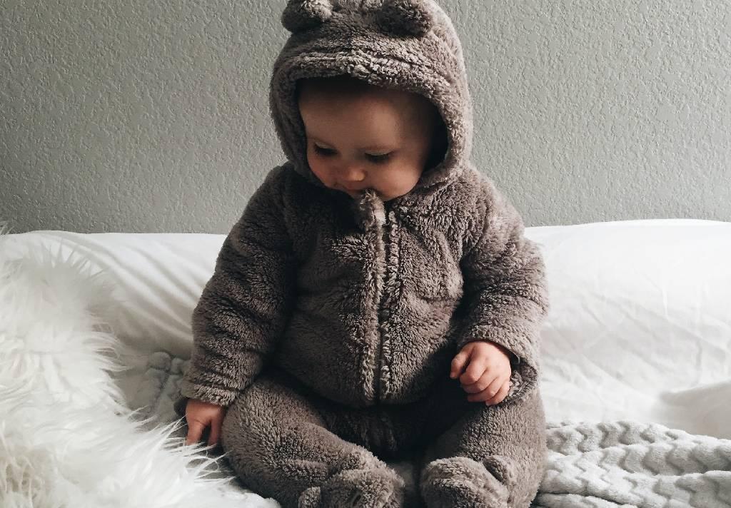 Vemos um bebê trajando uma roupa de ursinho (imagem ilustrativa).
