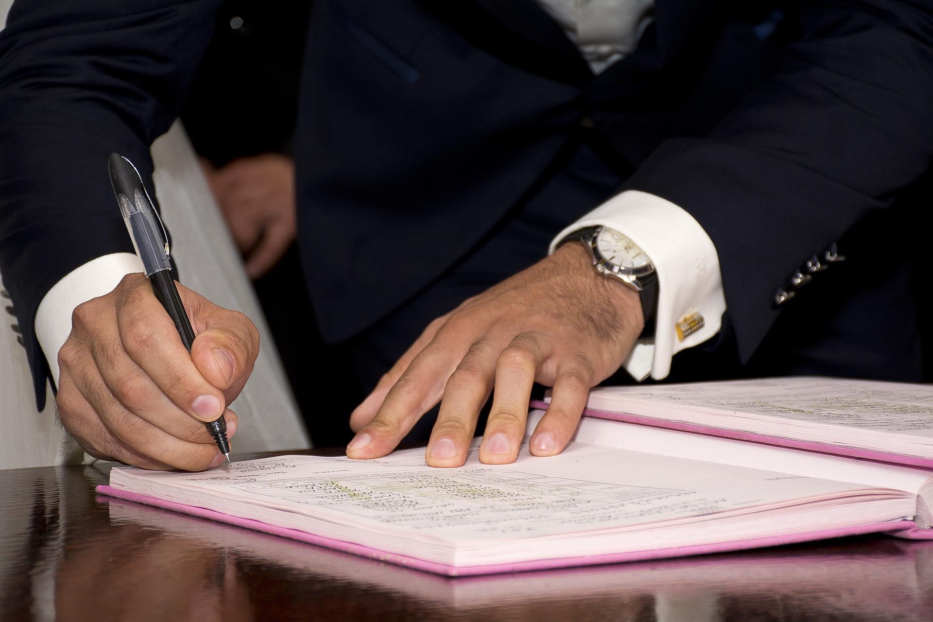 Vemos um homem assinando um documento (imagem ilustrativa).