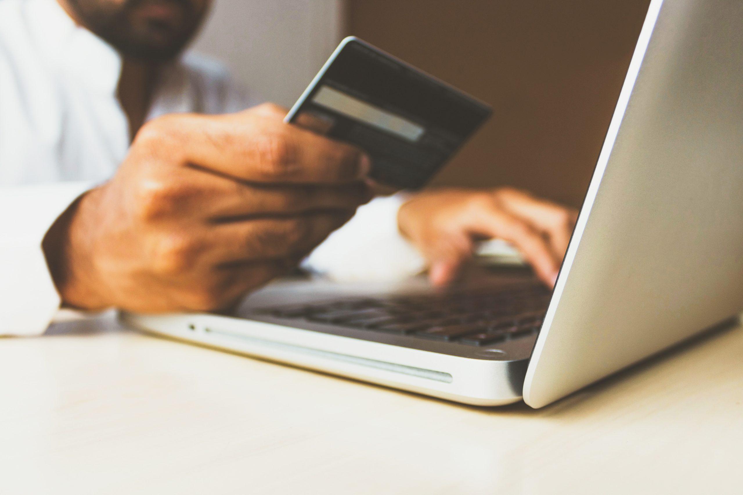 Imagem de um homem segurando um cartão de crédito em frente um computador.