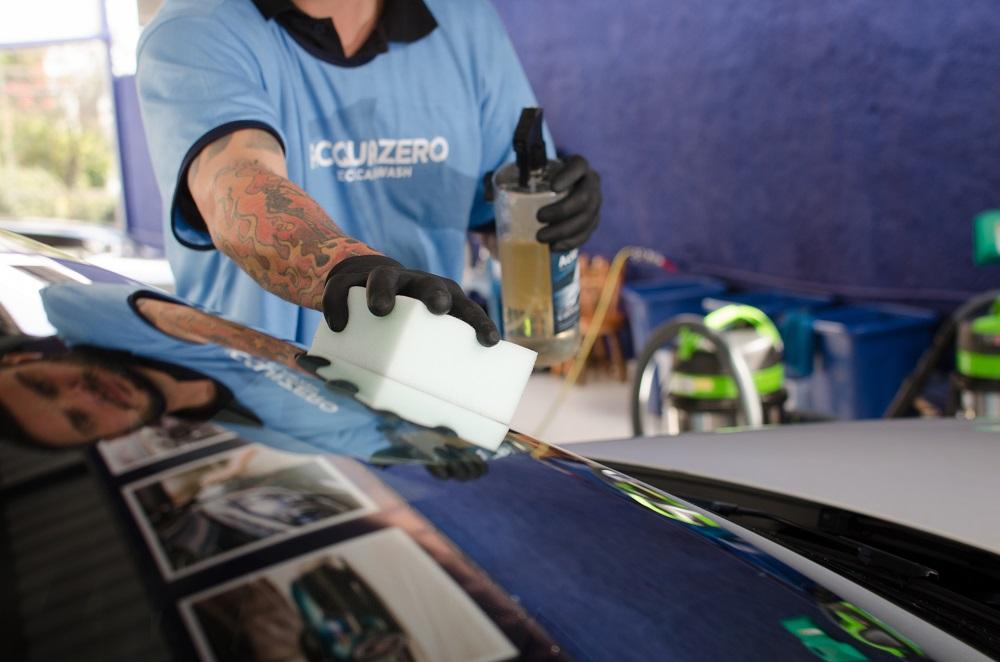 Funcionário da Acquazero com o uniforme da empresa fazendo a limpeza de um vidro de um carro. Ao fundo vemos uma parede azul e equipamentos. Imagem ilustrativa para texto franquia de estética automotiva.