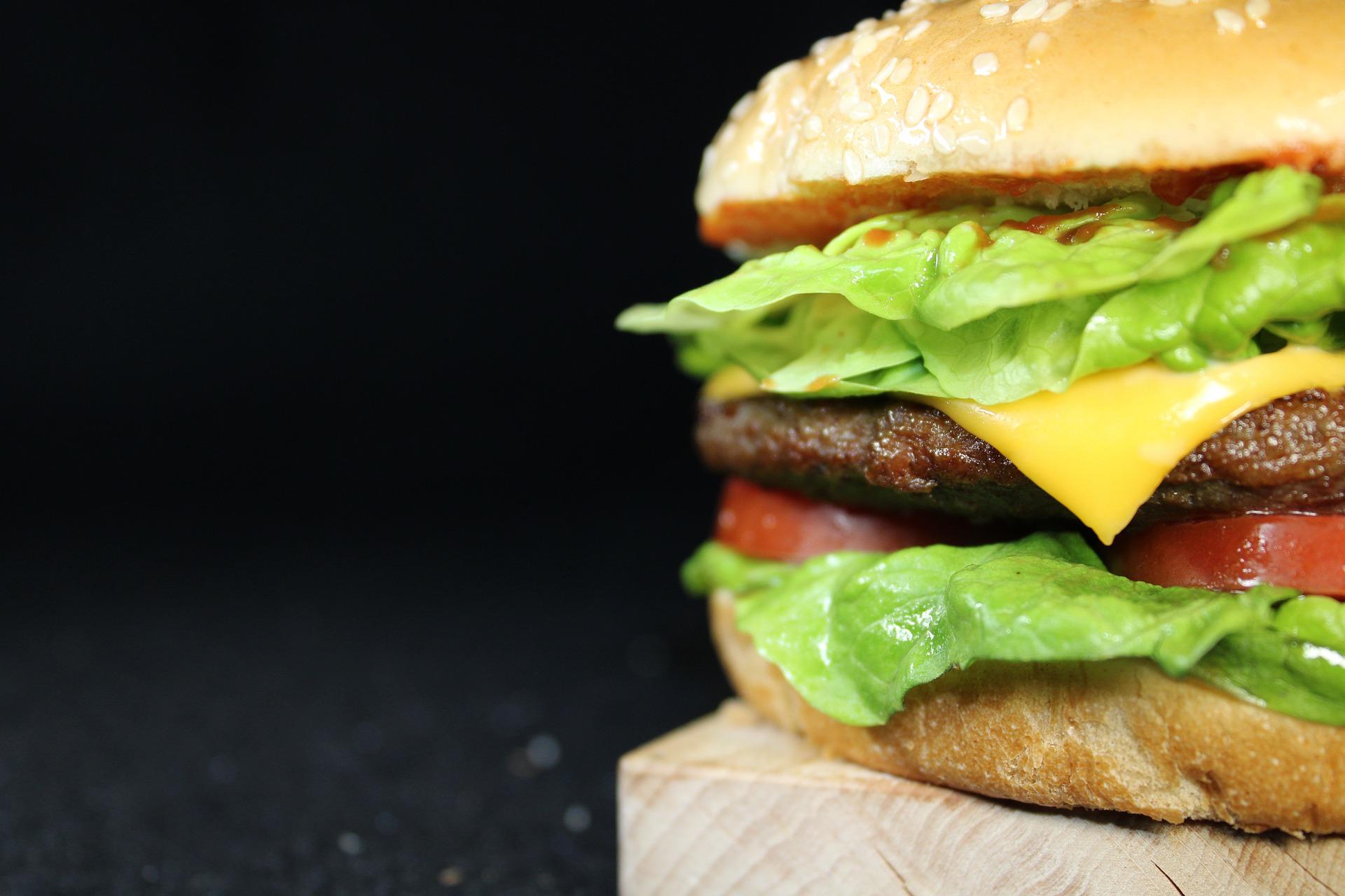 Vemos um hambúrguer com queijo, alface e tomate, em cima de uma tábua de madeira em um fundo preto (imagem ilustrativa). Texto: franquia do mcdonald's.
