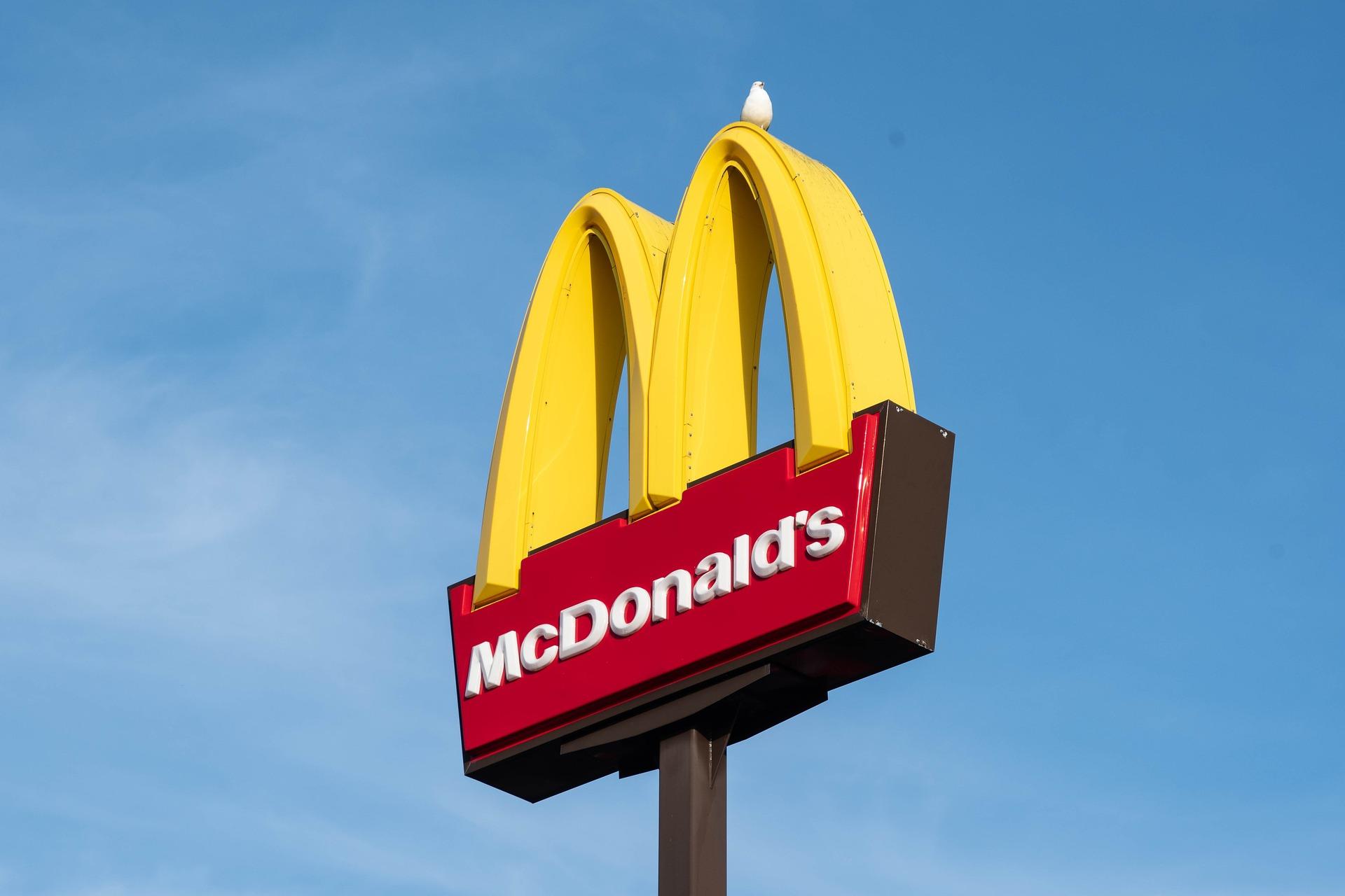 Vemos uma placa do McDonald's com um M amarelo e a parte inferior vermelha. Ao fundo temos um céu azul (imagem ilustrativa). Texto: franquia do mcdonald's.